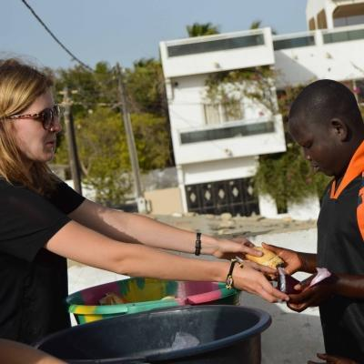 A volunteer hands out food while working with children in Senegal.